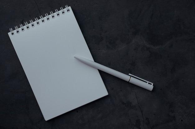 テクスチャと暗い背景にメモ帳とペンをきれいに。教育用またはテキスト用のスペースとビジネスのコンセプト。ノート、トップビューを書くためのホワイトペーパーとノート。