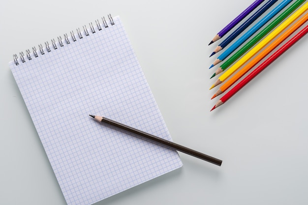 Clean notepad in a cage with a pencil lying on it and rainbow color pencils in the form of an arrow