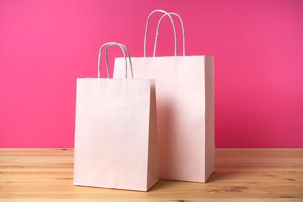Чистые бумажные розовые пакеты на ярко-розовом фоне. экология и покупка урана.