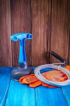 木の板の青いハンドルとケーブルでプラスチック製のプランジャーを掃除する下水道の掃除用の配管ツール
