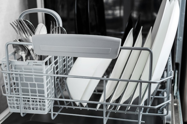 Чистые тарелки и другую посуду после мытья в посудомоечной машине