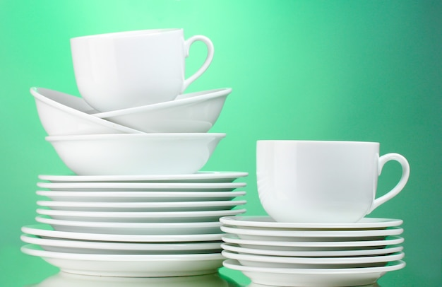 Clean plates, cups on green surface
