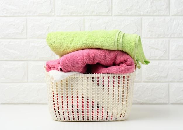 흰색 선반, 욕실 내부에 있는 플라스틱 바구니에 깨끗한 롤 테리 수건