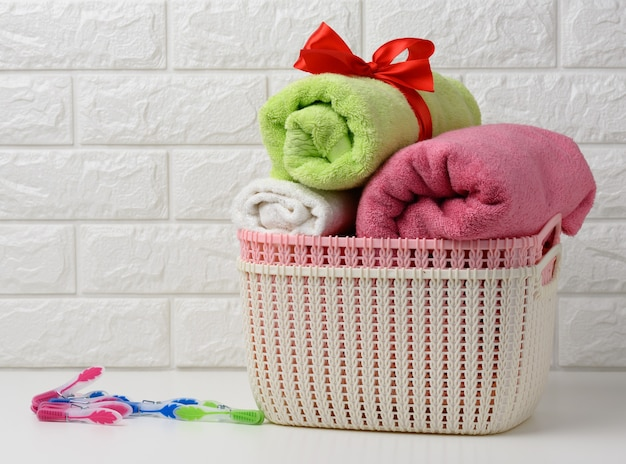 Clean rolled terry towels in a plastic basket on a white shelf, bathroom interior