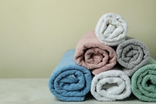asciugamani rotolati puliti su sfondo beige, spazio per il testo