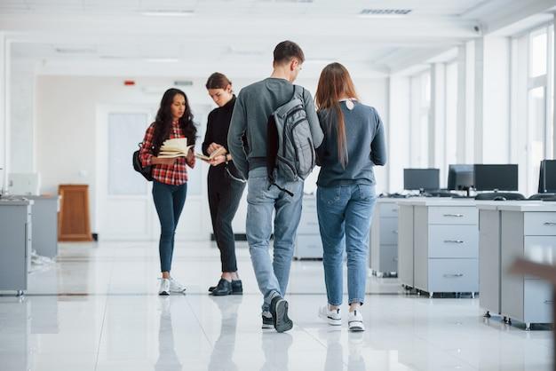 Чистая комната. группа молодых людей, идущих в офисе во время перерыва