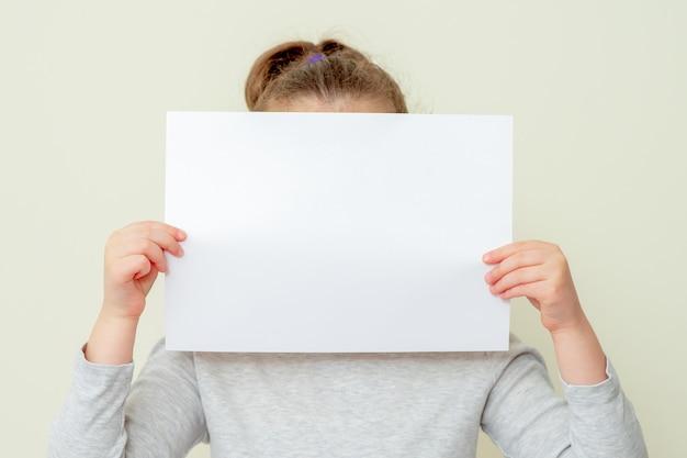 흰색 배경에 그녀의 얼굴을 덮고 아이의 손에 종이의 깨끗한 시트. 아이의 손에 있는 모형 종이.