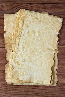 木製の表面の背景にしわくちゃの紙のきれいなシート