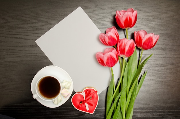 Clean sheet of paper, pink tulips and a mug of coffee.