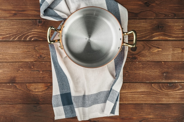 Clean shiny copper kitchenware on wooden board