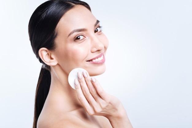 きれいな肌。白い壁にポーズをとって、笑顔で彼女の顔からファンデーションを削除する美しい明るい若い女性