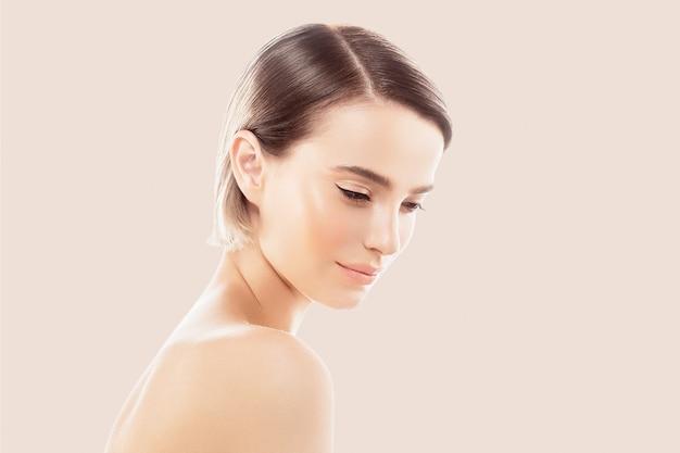 Чистый цвет кожи губ. белокурая концепция внимательности кожи коротких волос брюнетки. изолированные на бежевом фоне