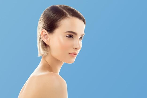 Чистый цвет кожи губ. белокурая концепция внимательности кожи коротких волос брюнетки. изолированные на синем фоне