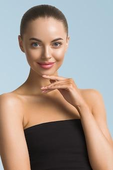 깨끗한 피부 여자 얼굴 아름다움 그을린 얼굴 아름다운 미소를 닫습니다. 파란색 배경입니다. 얼굴 만지기.