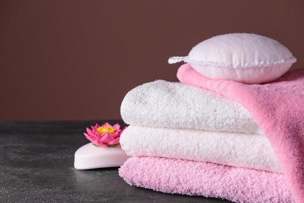 柔らかいタオル、石鹸、灰色のテーブルのウィスプをきれいにします
