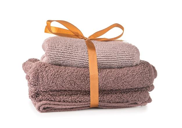 Чистые мягкие полотенца, перевязанные лентой на белом фоне