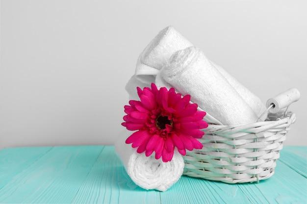 Чистые мягкие полотенца с цветком на деревянном столе