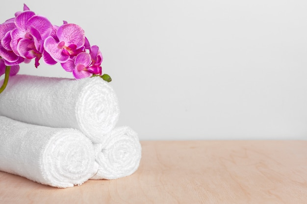 Clean soft towels with flower on wooden surface table