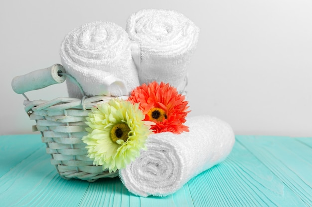Clean soft towels with flower on wooden table