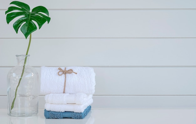 복사 공간이 있는 흰색 테이블에 깨끗한 스파 수건과 식물을 심으세요.