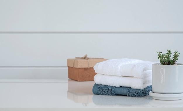 Чистые полотенца спа на белом деревянном столе в ванной комнате с космосом экземпляра.