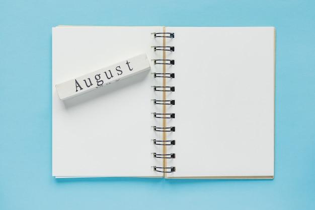 ノートとメッセージと8月の木製カレンダーバーのきれいなスパイラルノートブック。最小限のビジネスフラットレイ