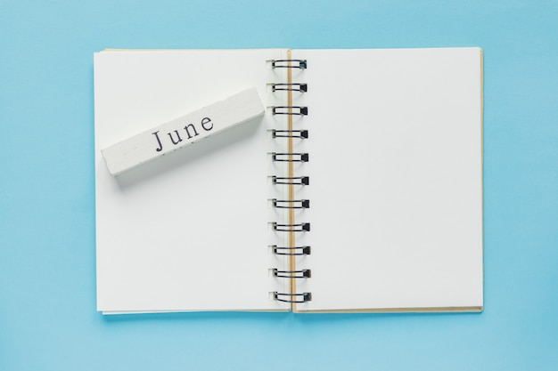 Clean spiral note book for notes and messages and june wooden calendar bar