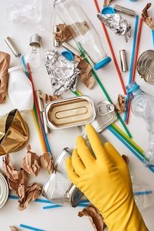 Очистите мир. положите оранжевую перчатку под мусор. на полу разный несортированный мусор. пластик, банки, бумажный мусор перемешиваются вместе
