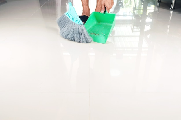 Clean tiled floors with a plastic broom and dustpan