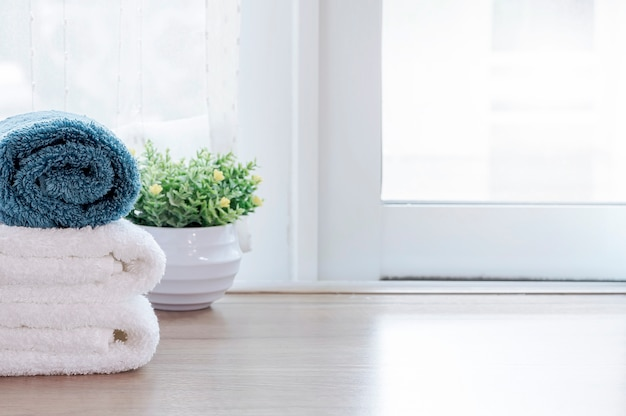 Clean towels and houseplant on wooden table in modern room. copy space.