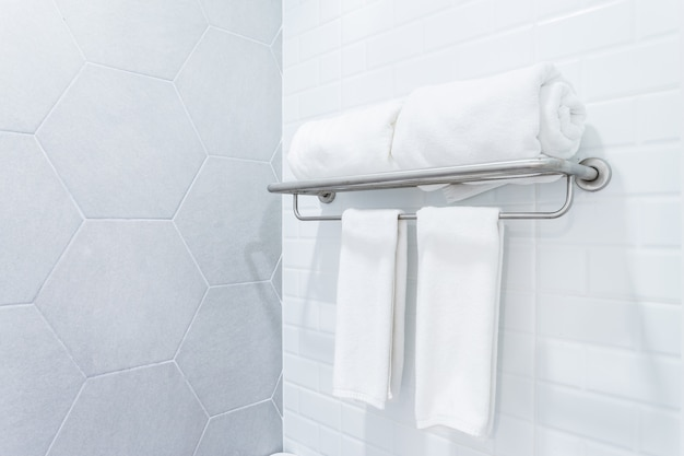 Clean towels with hanger on wall bathroom interior background.