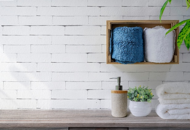 Clean towels with soap dispenser on shelf and wooden table in bathroom, white brick wall background