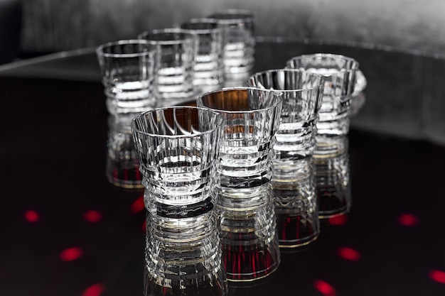 Clean transparent faceted drink glasses stand on a black