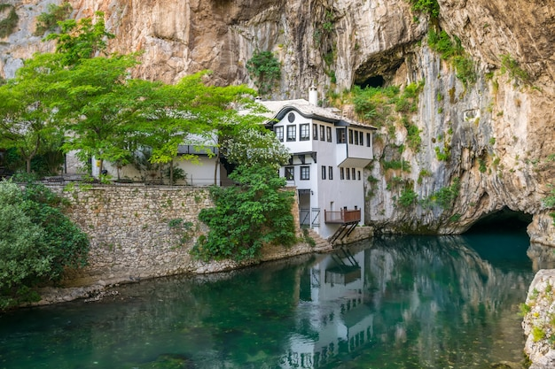 A clean underground river emerges from a cave near an islamic mosque