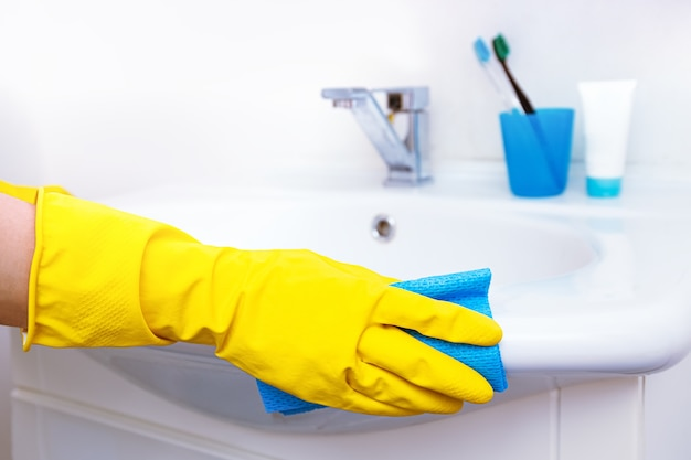 집 청소하기. 여자 화장실에서 집안일을하고, 노란색 장갑에 손을 물 꼭지, 강철 싱크대 witth 파란색 걸레 및 세제 스프레이 청소.