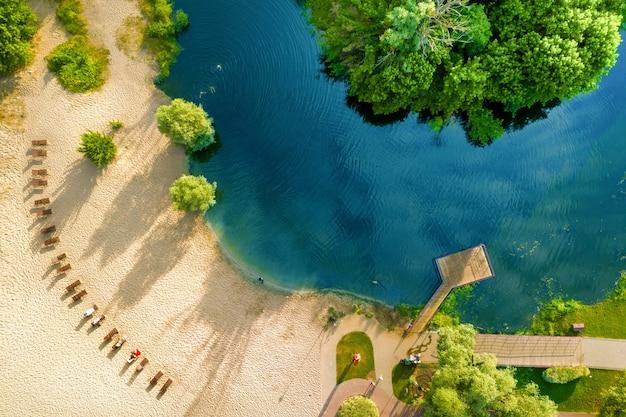 강과 녹색 해안 옆의 깨끗하고 따뜻한 모래 사장. 푸른 물, 무인 항공기 보기.