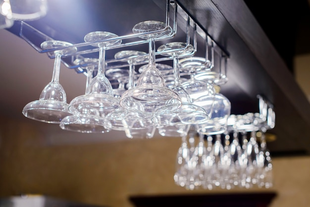 Clean washed and polished glasses hanging over a bar rack.