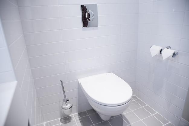 きれいな白いバスルームの背景室内装飾ミニマリストスタイル、オープンスペース。本物の写真。セラミックトイレ付きのモダンな白いバスルーム。