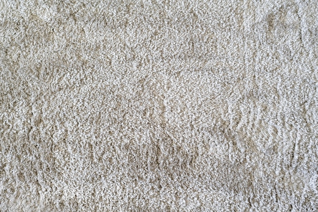 A clean white color carpet on the floor at home in living room, textile texture