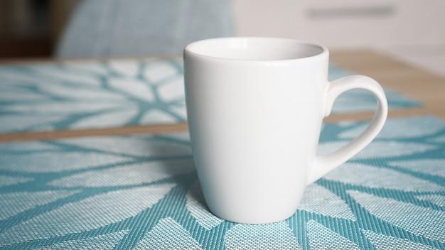 後ろの青いテーブルの上にハンドルが立っているきれいな白いマグカップ
