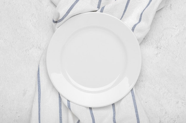 Clean white plate on fresh towel with stripes on a stone light minimalist background.