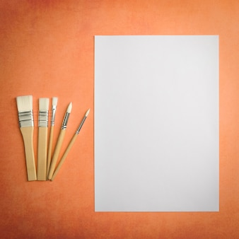 A clean white sheet and brushes on a textured background with space to copy layout mockup space