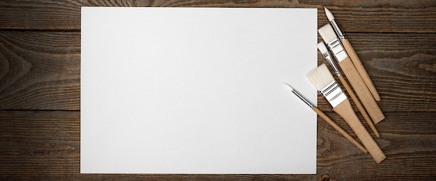 A clean white sheet and brushes on a wood textured background