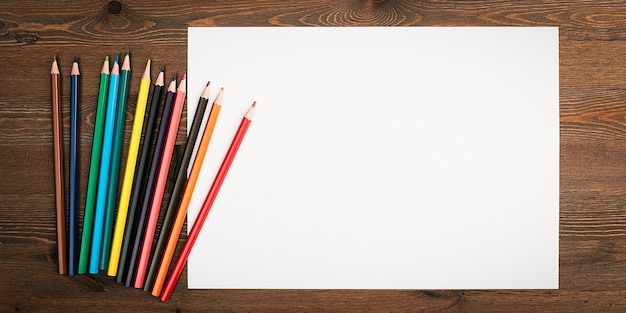 A clean white sheet and colored pencils on a wood textured background