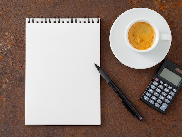 Clean white sheet in an open spiral-bound pad, pen, calculator and cup of coffee on the iron