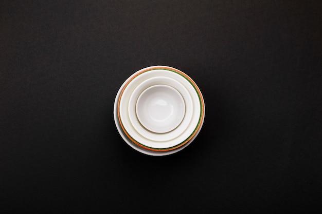 Clean white tableware on black. top view