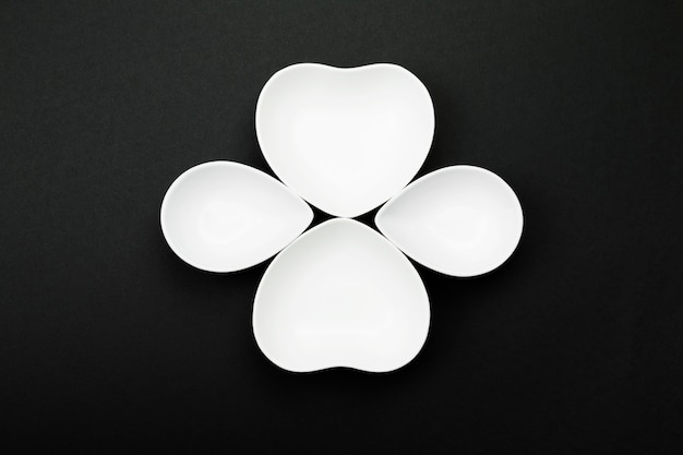 Clean white tableware in form of clover on black. top view