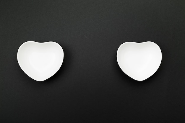Clean white tableware in form of heart on black. top view, copy space