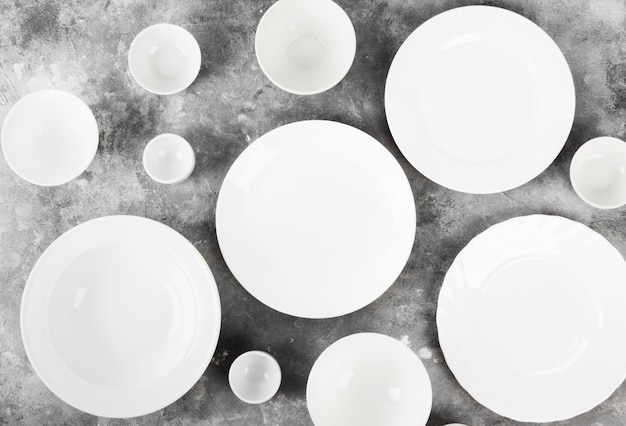 Clean white tableware on a gray background. top view