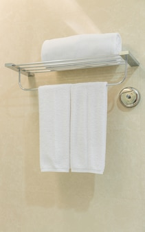Clean white towel on a hanger prepared in bathroom .